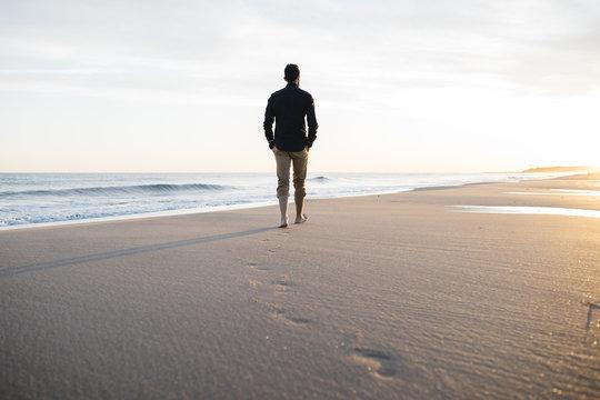 walking on beach at sunset