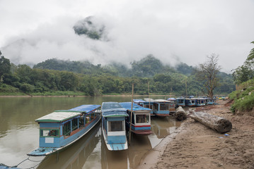 Wooden boats in laos river with fog and mountain background,beautiful landscape,Nong Khiaw,Muang Ngoi in Laos.