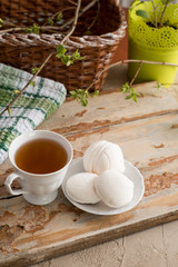 Beautiful composition with cup of tea and marshmallow. Spring Breakfast. A cup of tea with a white marshmallow on a wooden background. Sprigs of a tree with green buds and leaves.
