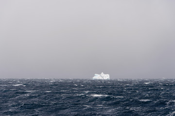 Iceberg in stormy Antarctic sea