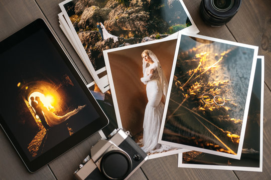 Printed wedding photos with the bride and groom, a vintage black camera and a black tablet with a picture of a wedding couple