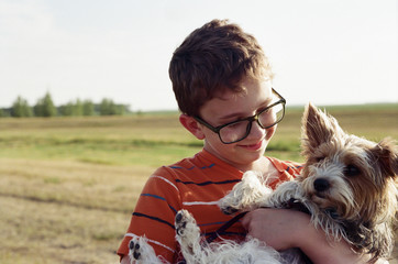 Smiling boy carrying Yorkshire Terrier on field