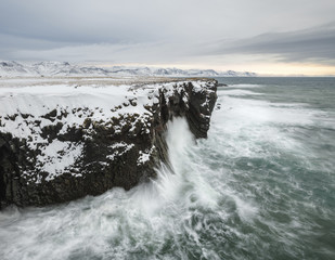 Majestic view of waves splashing on rock formations in sea during winter