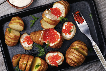 Baked potatoes with Dutch sauce and red caviar on a tray, top view