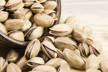wooden bowl of pistachios on wooden background
