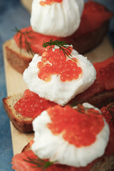 Delicious sandwich with egg - poached, caviar and red fish