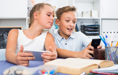 Girl is watching a video with a boy in his smartphone