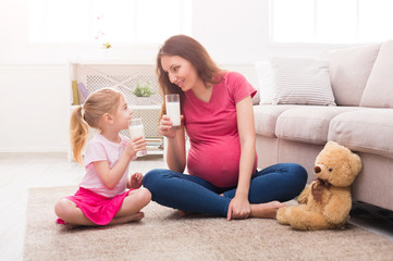 Little girl and her mom drinking milk at home