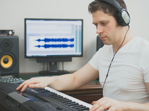 Handsome man recording song in music studio.
