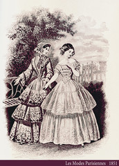 1851 vintage fashion, French magazine Les Modes Parisiennes presents two ladies walking leisurely outdoor in a beautiful garden with fancy cloths and hairdressing