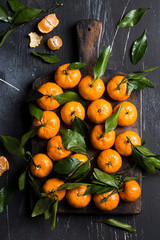 Tangerines with green leaves on wooden board on dark background