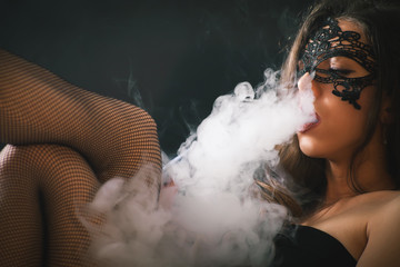 Young, beautiful girl smoke a hookah at club