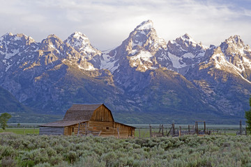 Famous barn beneath snow capped mountain in the Grand Tetons.