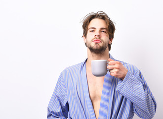 Guy in home or bath clothes drinks tea or coffee.