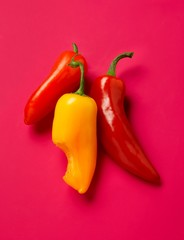 Bright red and yellow peppers on pink background