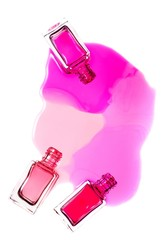 Spilled pink nail polish and bottles on white background