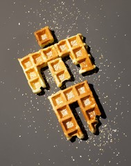 Waffle pieces shaped like a person gray background