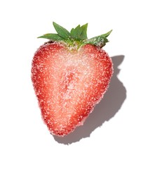 Strawberry half sprinkled with sugar on white background