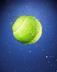 Tennis ball submerged with water drops on blue background