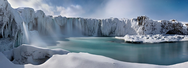 Godafoss frozen waterfall during Winter at sunset. North Iceland