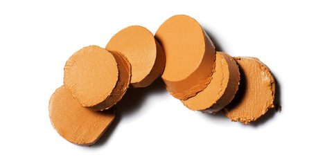 Circular slices of of brown cosmetics on white background