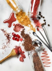 Jars of spices and powdered cosmetics spilled on white background