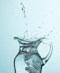 Water splashing into glass pitcher