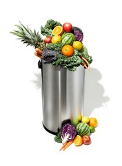 Fresh fruits and vegetables in trash can on white background