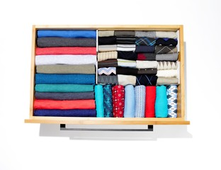 Top view organized drawer of neat folded socks and clothing on white background