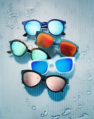 Sunglasses frames with colorful lenses against background with water drops