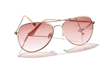 Sunglass frames with cracked pink lenses against white background