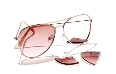 Sunglasses with broken pink lenses  against white background