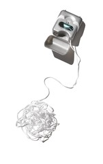 Ball of tangled white dental floss with container box on white background