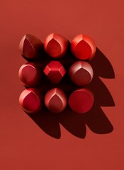 Nine red lipstick pieces on red background