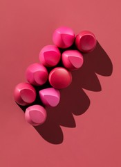 Nine pink lipstick pieces on pink background