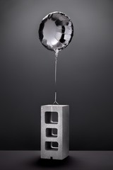 Metallic silver balloon tied to cement block on gray background