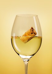 Cork floating in glass of white wine on yellow background