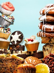 Stacked muffins, cupcakes and sweet buns with dripping icing studio shot