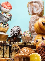 Stacked muffins, cupcakes, cake and sweet buns with icing studio shot