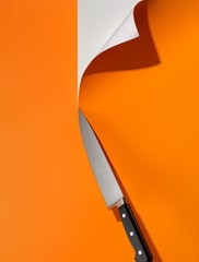 Sharp knife cutting through orange paper on white background
