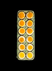 Top view carton of halved boiled eggs on black background