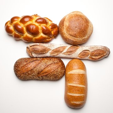Variety of fresh bread loaves on white background