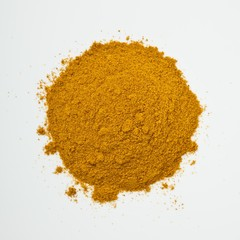 Pile of yellow curry powder on white background