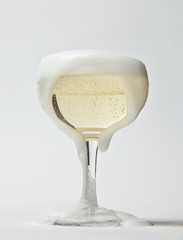 Foam overflowing full glass of champagne studio shot