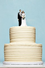 White wedding cake topped with bride and groom figurines