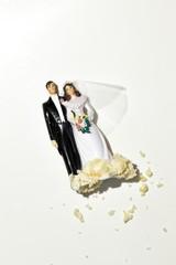 Wedding cake bride and groom figurines on white background