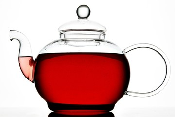 Glass teapot with red liquid on white background