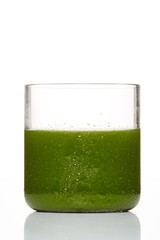 Glass of green juice with condensation on white background