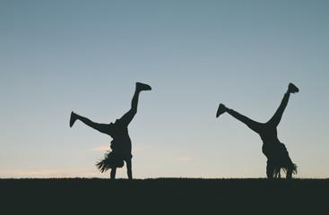 Little girl silhouette doing cartwheels