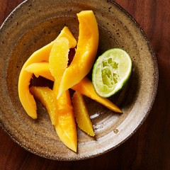 Bowl of mango and orange slices with lime wedge
